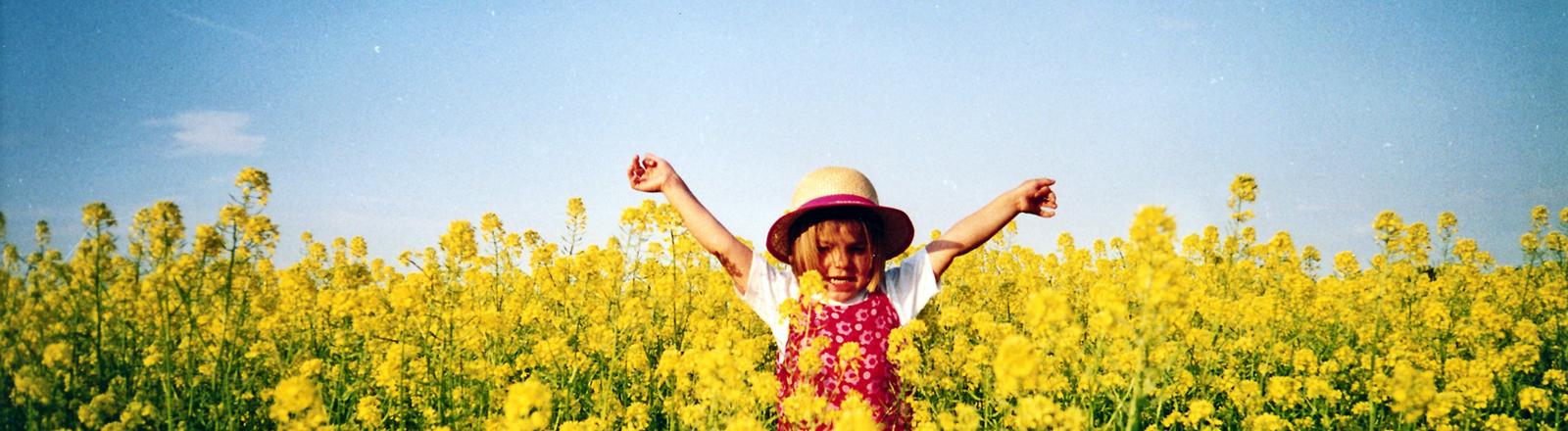Ein Mädchen spielt in einem Rapsfeld.