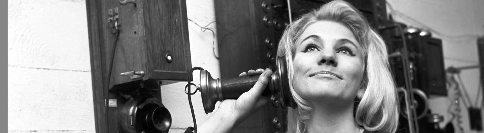 Eine Frau telefoniert mit einem historischen Telefonapparat.