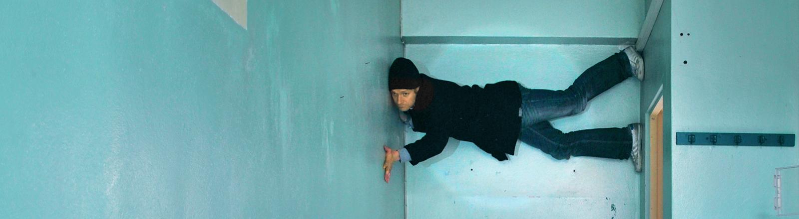 Ein Mann hält sich waagerecht zwischen zwei Wänden mit Füßen und Händen fest.