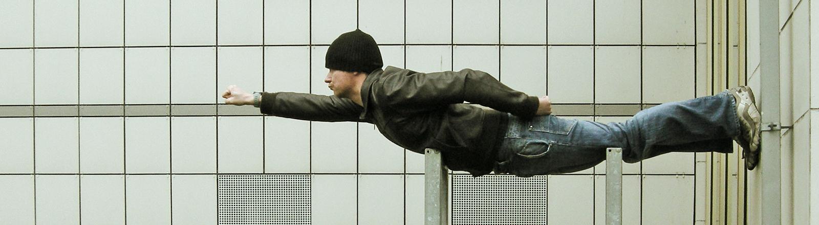 Ein Mann liegt waagerecht auf zwei Pfosten, er streckt den rechten Arm nach vorne. Er sieht aus wie ein fliegender Superheld.