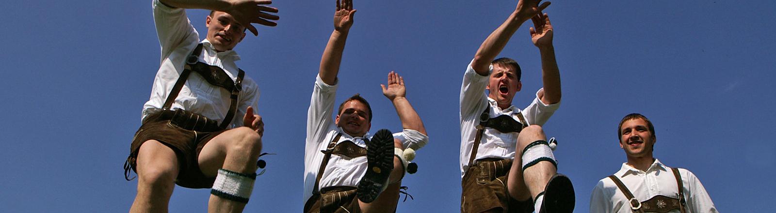 Vier Männer in Lederhosen und weißen Hemden springen in die Luft und reißen die Arme in die Höhe.
