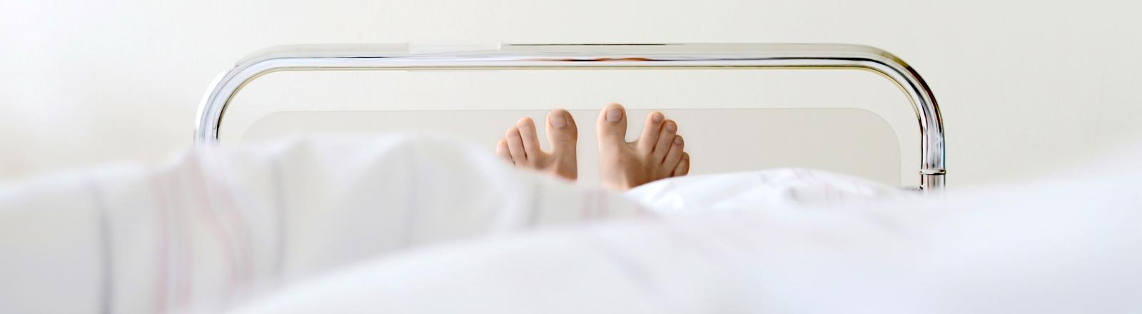 Zwei Füße schauen unter einer Decke heraus, die Person liegt in einem Krankenbett.