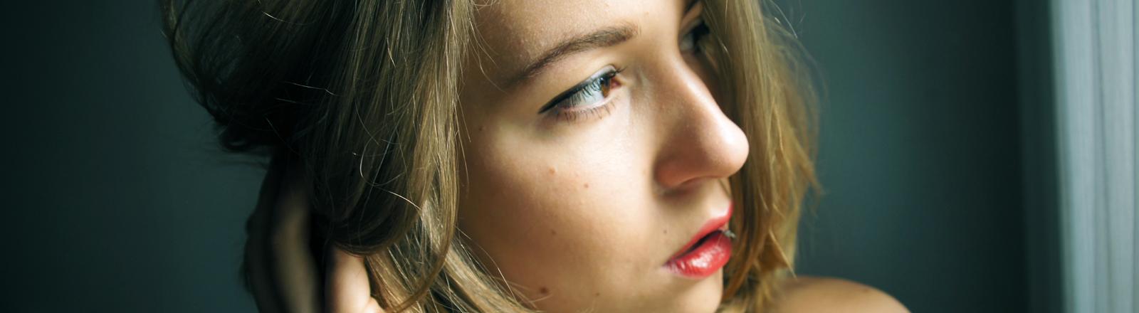 Ein Frau blickt kritisch aus dem Fenster.