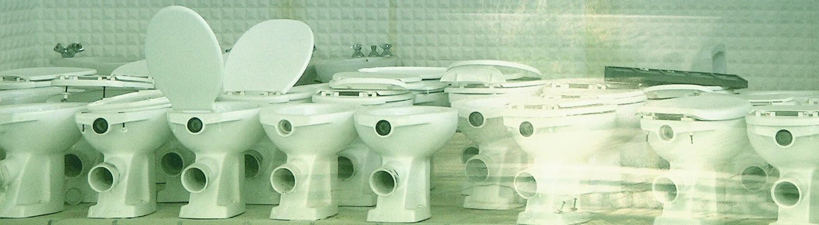 Eine Reihe Toilettenschüsseln in einem Schwimmbad
