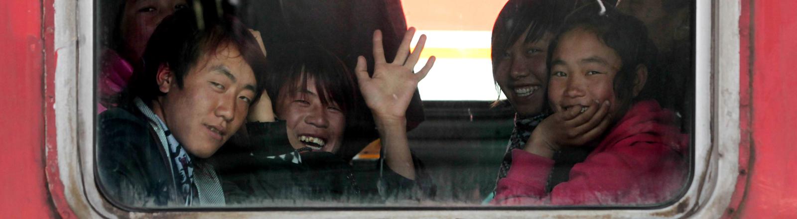 Junge Chinesen sitzen in einem Zugabteil und schauen aus dem Fenster.