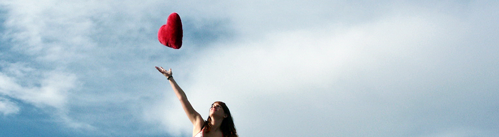 Eine Frau wirft ein Plüschherz in die Luft.