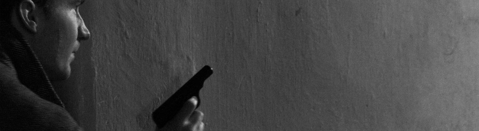 Ein Mann mit Pistole lugt um die Ecke.