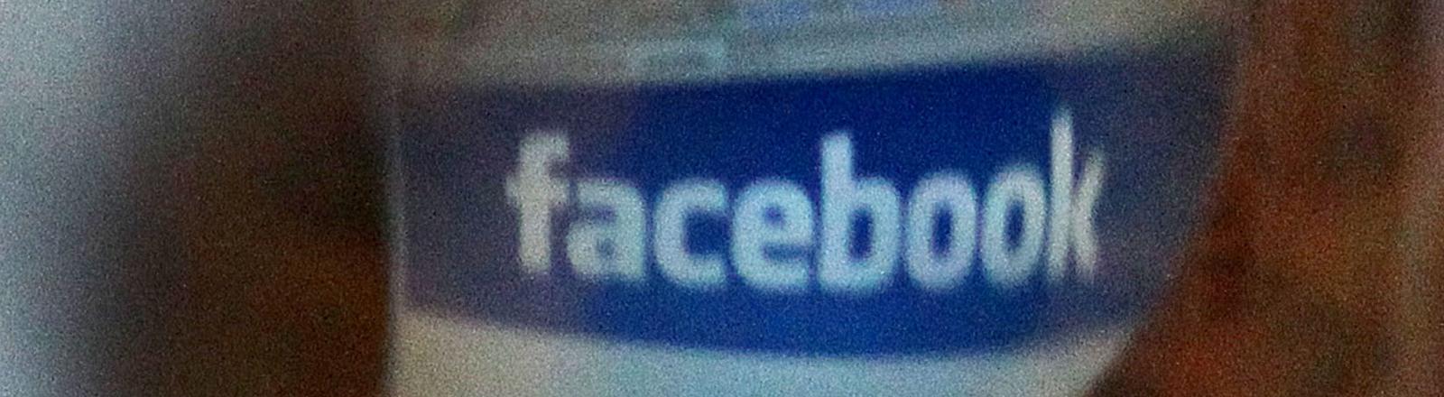 Das Facebook-Logo spiegelt sich in der Iris einer Betrachterin.