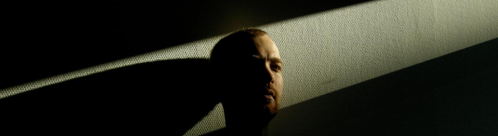 Ein Mann steht im Dunkeln an einer Wand und wird von einem Lichtstrahl beleuchtet.