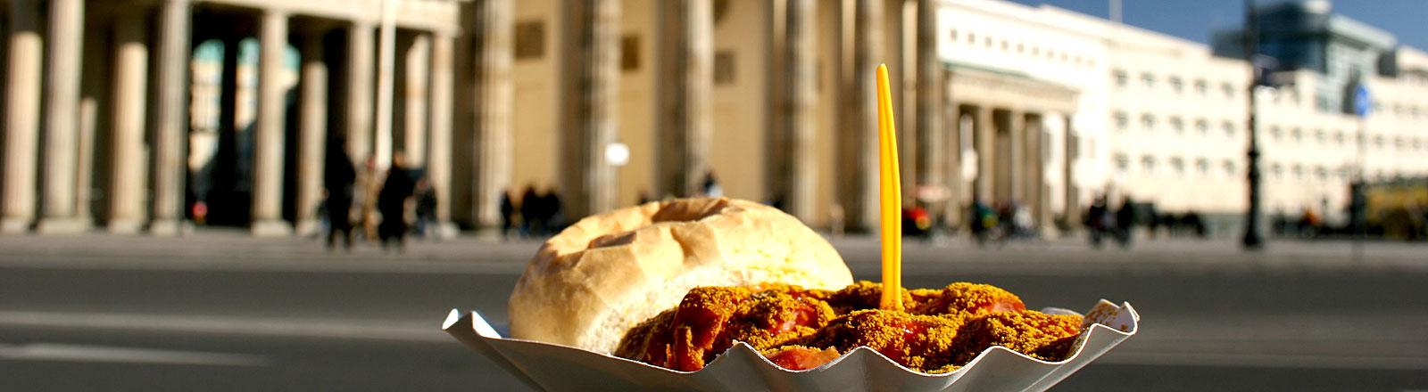 Currywurst mit Brötchen, positioniert vor dem Brandenburger Tor