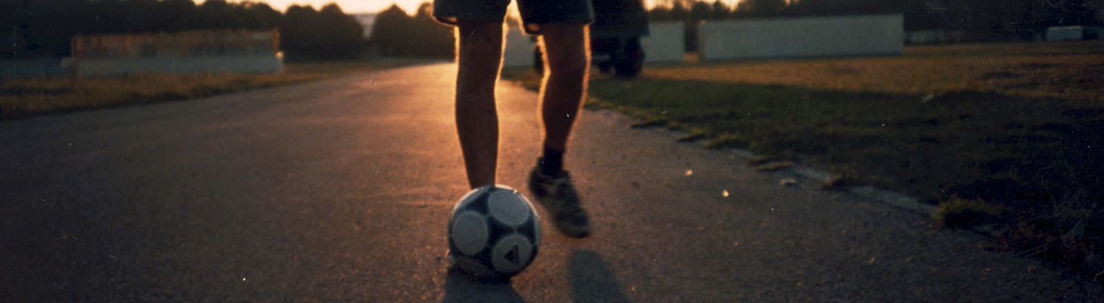 Beine eines Mannes, der einen Fußball vor sich her tritt. Es herrscht Abendstimmung, die Sonne leuchtet im Hintergrund.