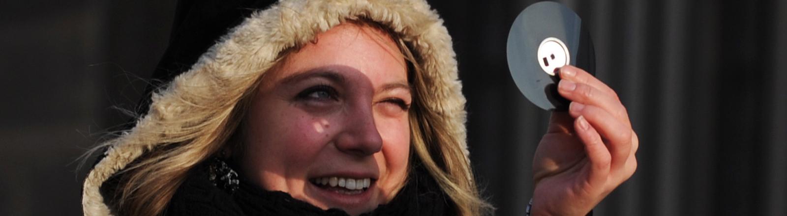 Eine Frau schaut durch das kleine Loch einer Floppy-Disk eine Sonnenfinsternis an.