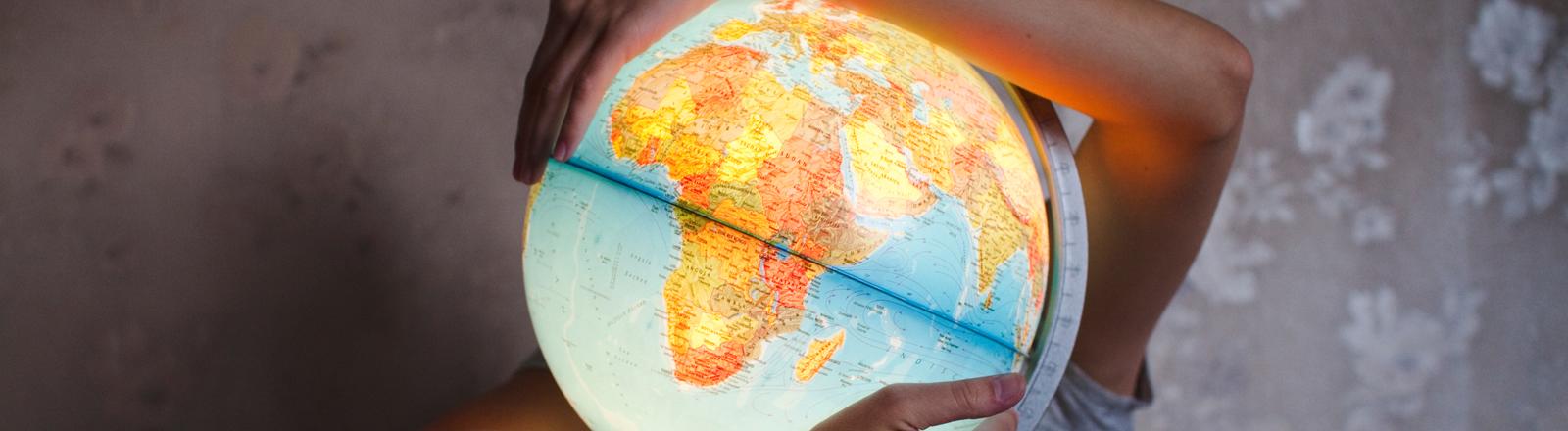 Ein Mann umfasst einen beleuchteten Globus.