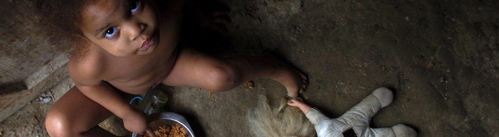 Die drei Jahre alte Ana Luisa aus Santo Domingo isst eine Portion Reis.