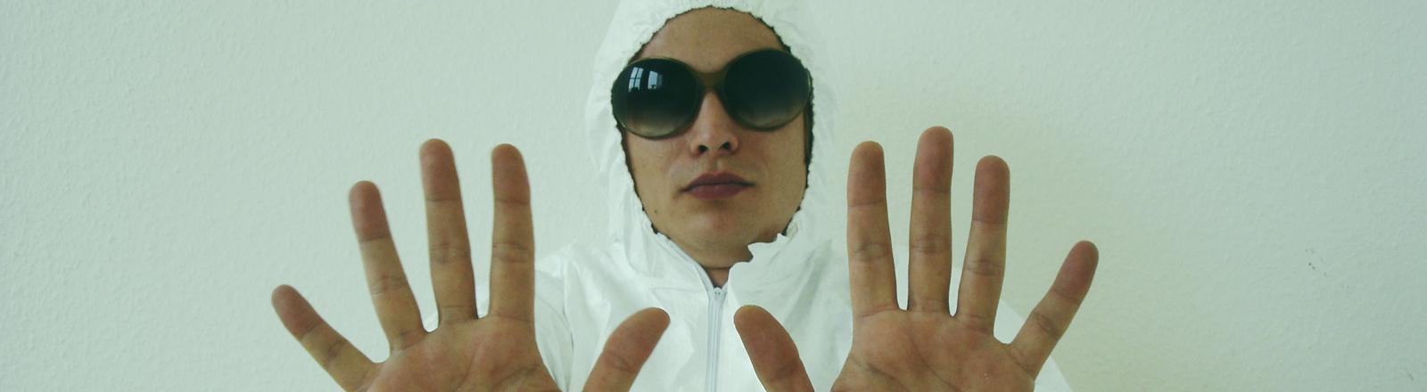 Ein Mann in einem weißen Schutzanzug und schwarzer Brille hält die Hände schützend vor sich.