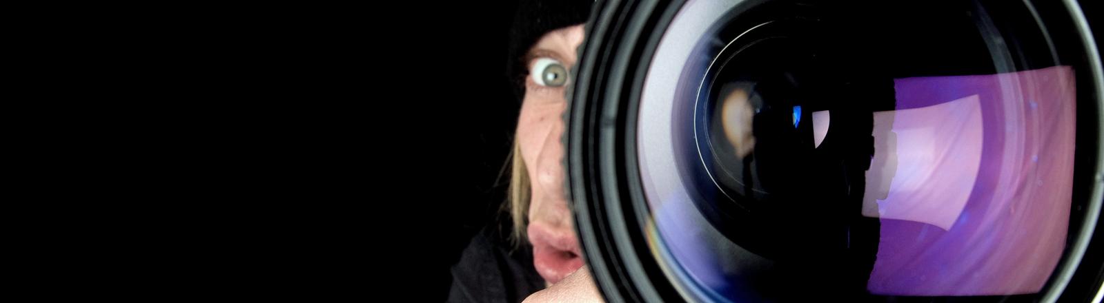Ein Mann schaut durch seine Kamera und macht dabei ein recht dümmliches Gesicht.