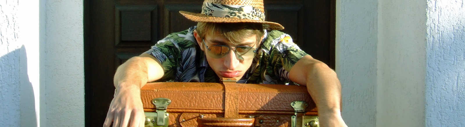 Ein Mann sitzt frustriert und gelangweilt auf einer Türschwelle, er trägt Urlaubskleidung und hat einen großen Koffer auf den Knien.
