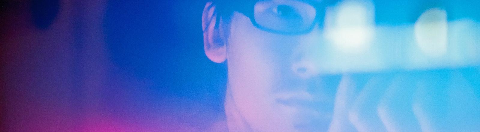 Ein Mann mit Brille spiegelt sich in seinem Monitor.