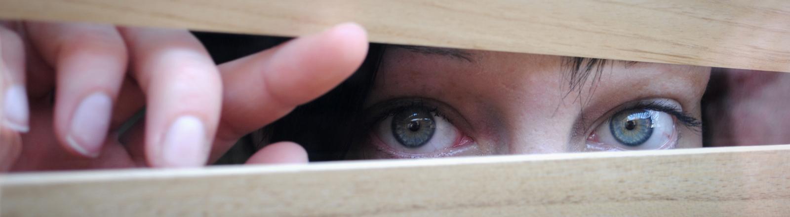 Eine Frau schaut heimlich und neugierig durch ein Fenster, sie linst durch die Jalousien.