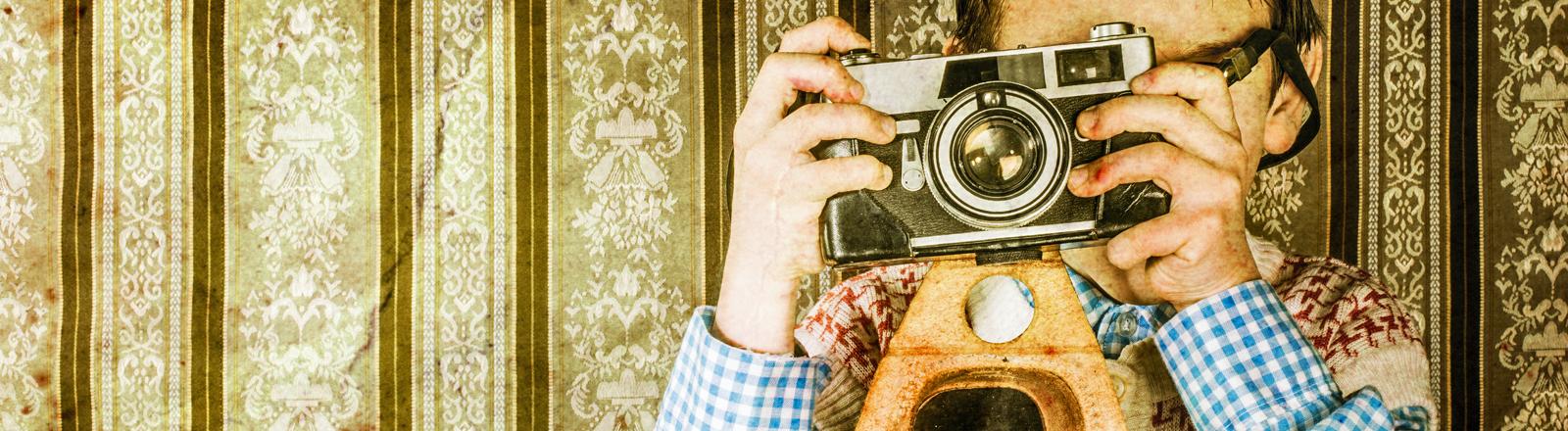 Vor einer grauseligen Tapete steht ein Junge mit einer alten Kamera. Ziemlich retro.