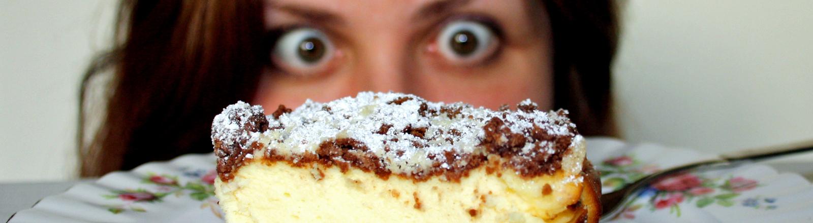 Eine Frau starrt mit weit aufgerissenen Augen auf ein köstlich aussehendes Stück Kuchen.