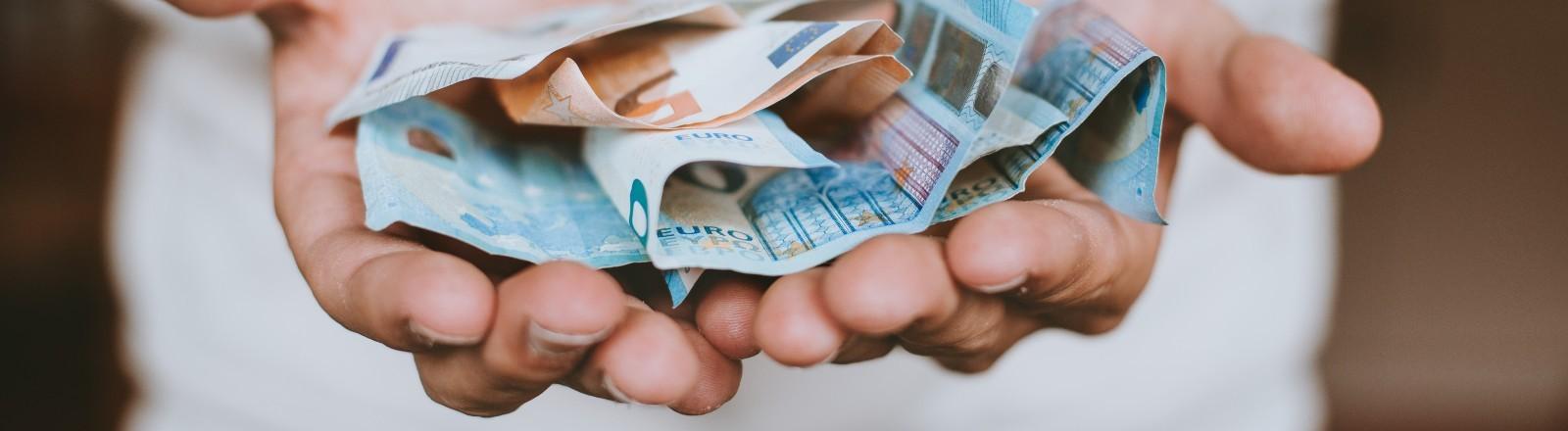Ein Mann hält mehrere Euroscheine in seiner Hand.