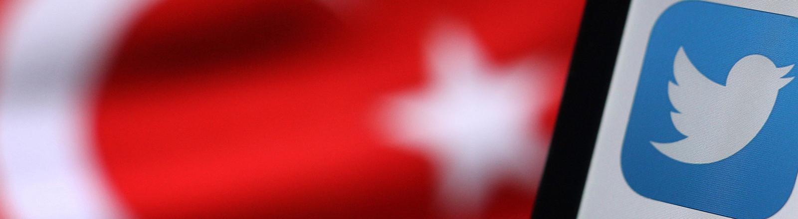 Im Hintergrund ist die türkische Flagge zu sehen, im Vordergrund das Twitterlogo.