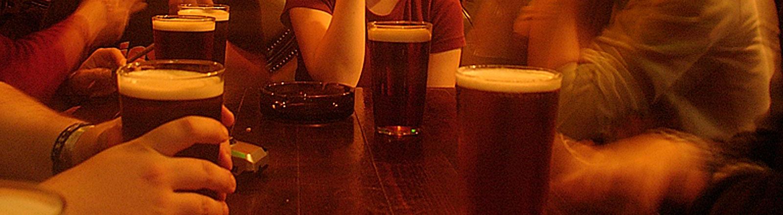 Biergläser in einer Kneipe am Tisch mit Jugendlichen