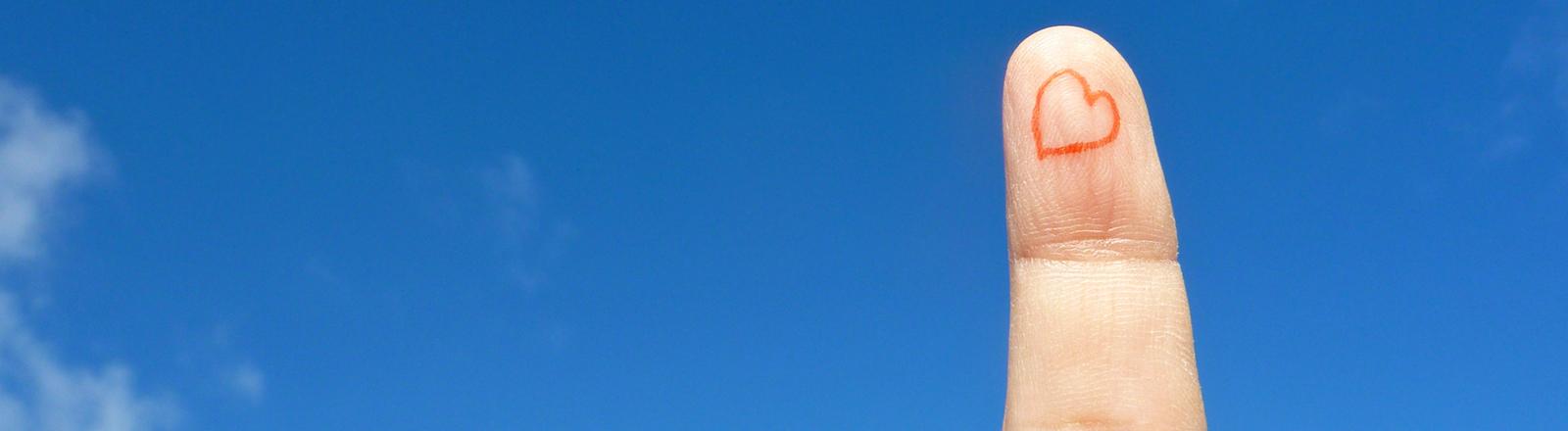 Ein Finger auf dem ein rotes Herz gemalt ist vor blauem Himmel.