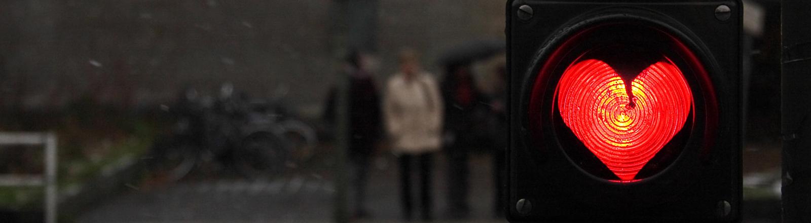 Die Anzeige einer Ampel zeigt ein rot leuchtendes Herz, im Hintergrund warten Fußgänger an einem Übergang.