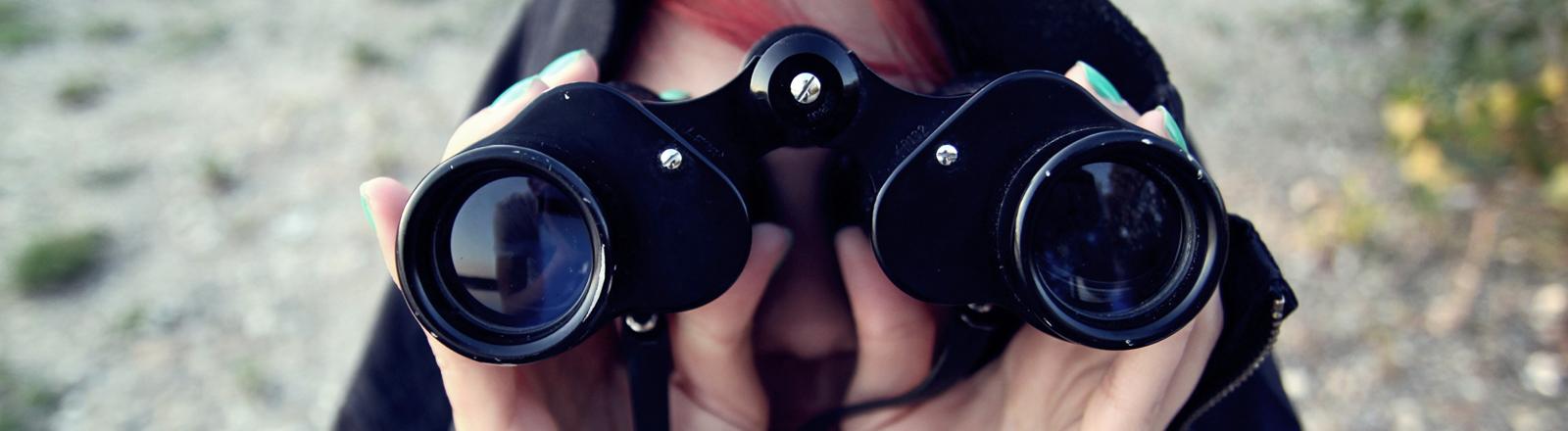 Eine Frau hat eine Decke über den Kopf gezogen und hält mit beiden Händen ein Fernglas an die Augen. Sie hat grün lackierte Fingernägel.