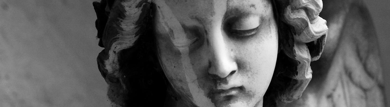 Statue eines weiblichen Engels mit gesenktem Blick.