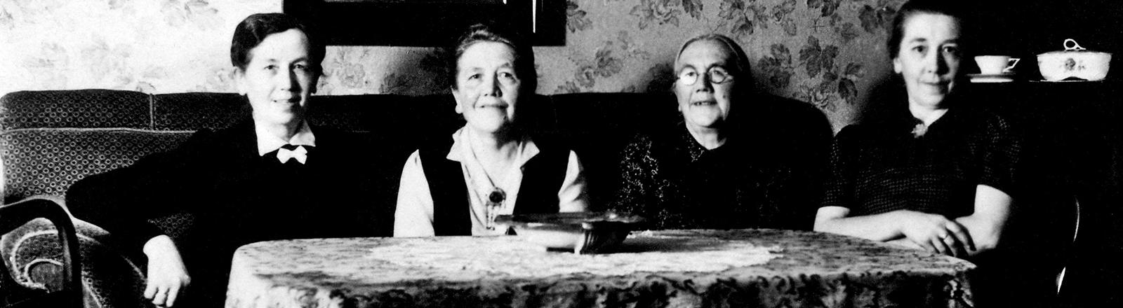 Schwarz-weiß-Foto. Zwei alte Frauen sitzen nebeneinander, vor ihnen ein Tisch mit Decke. Im Hintergrund ein Schrank mit Porzellan.