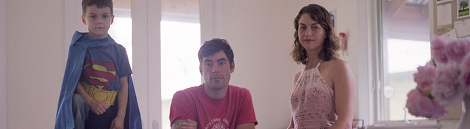 Ein Junge im Superman-Anzug steht neben Vater und Mutter.