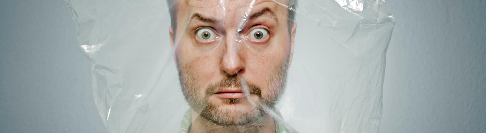 Ein Mann hat sich eine durchsichtige Plastiktüte über den Kopf gezogen und schaut direkt in die Kamera.