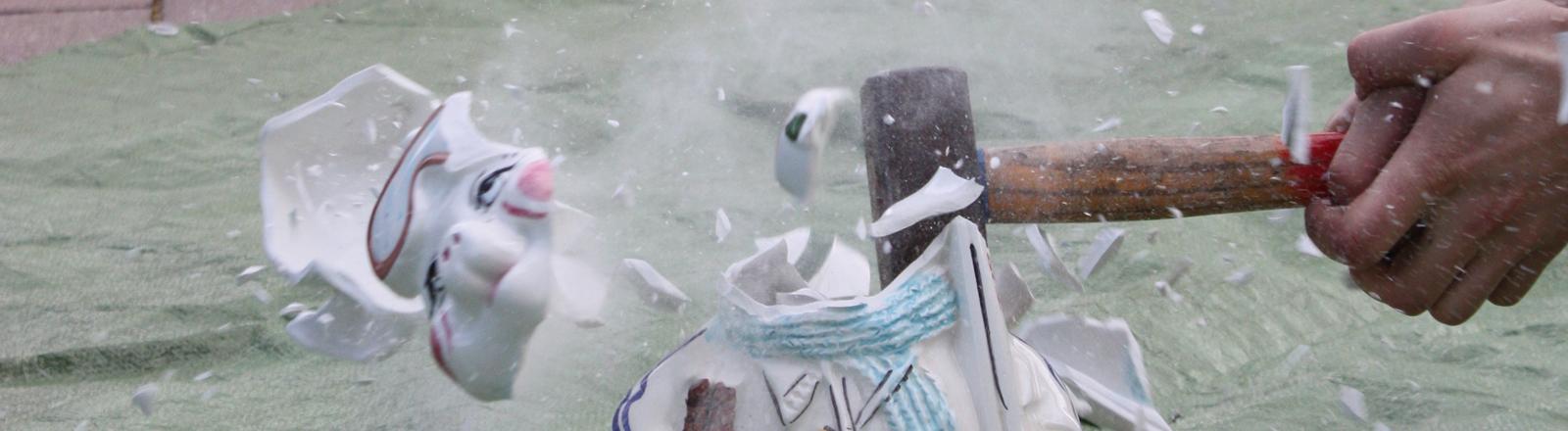 Eine Porzellanfigur wird mit einem Hammer kaputtgeschlagen