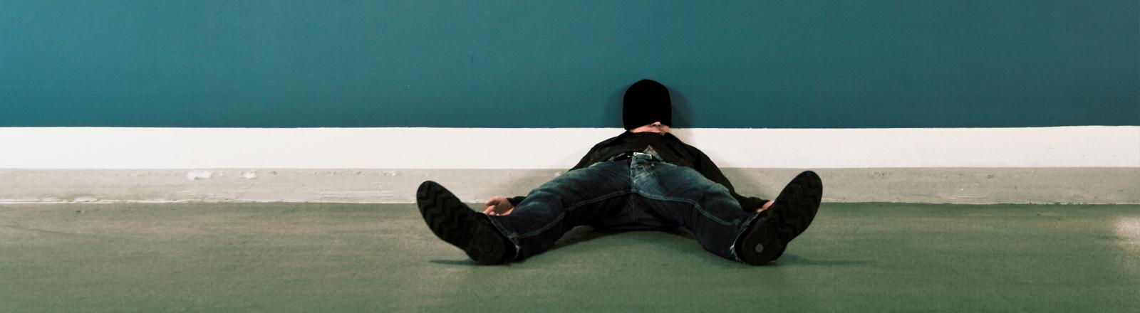 Ein Mann liegt auf dem Boden. Es wirkt so, als ob er schläft.