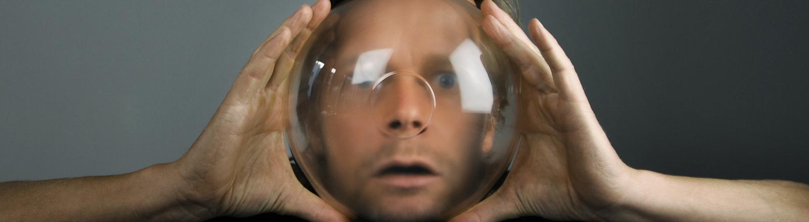 Ein Mann hält sich eine Glasschüssel vor das Gesicht