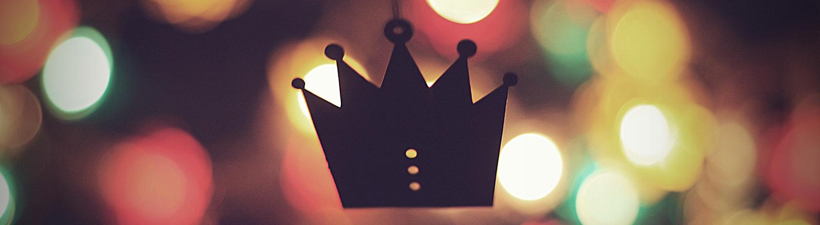 Eine Krone aus Pappe oder einem anderen Material hängt an einem Faden
