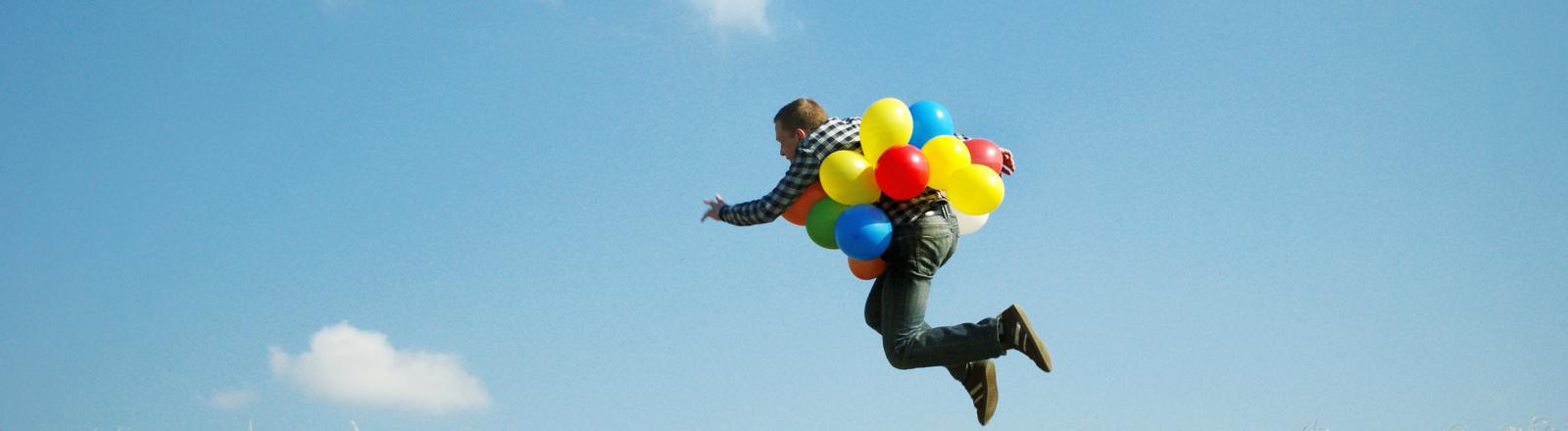 Mann fliegt mit Balons