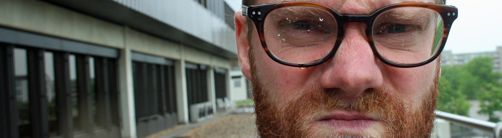 Christian Schmitt steht auf der DRadio-Wissen-Terrasse im Regen und ist sauer.