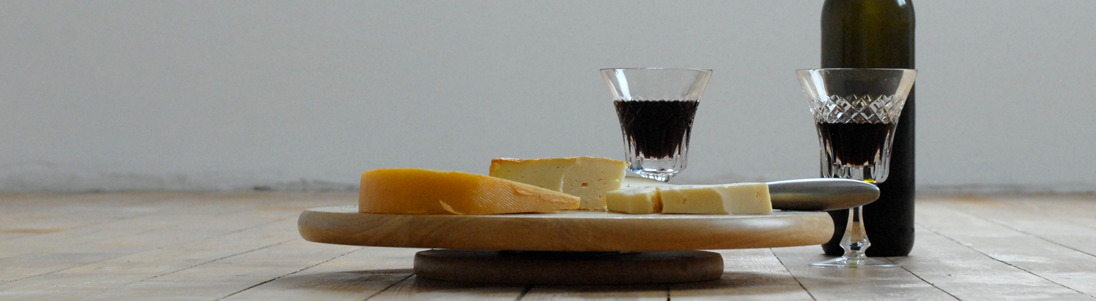 Rotweinflasche, Rotweingläser und Käse stehen auf einem Holzboden.