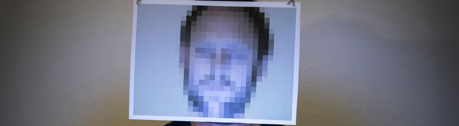 Ein Mann sitzt mit verpixeltem Gesicht vor seinem Computer.