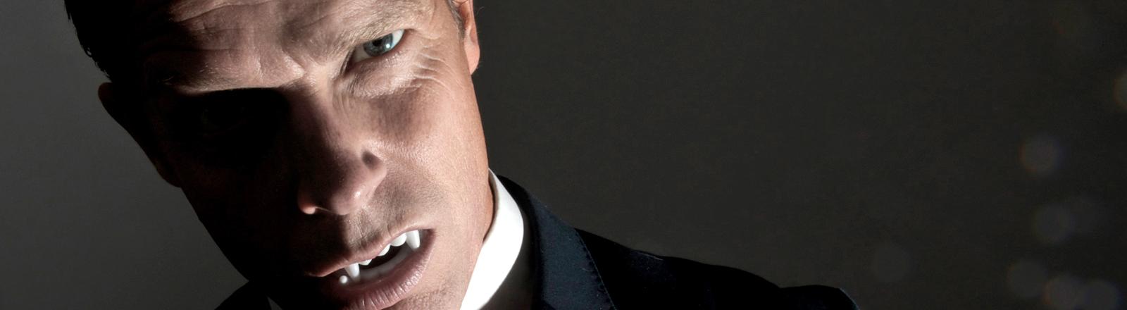 Ein Mann schaut grimmig in die Kamera. Er hat den Mund leicht geöffnet und zeigt lange Eckzähne.