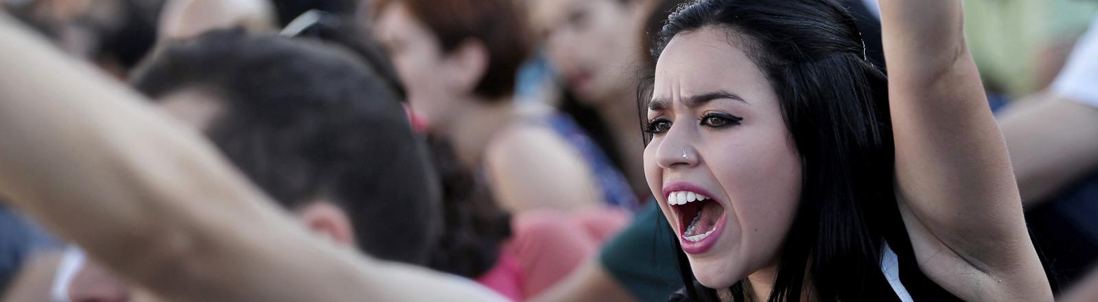 Eine junge Frau streckt ihren linken Arm in die Höhe und ruft etwas. Sie sitzt inmitten einer Menschenmenge. Juni 2013; Bild: dpa