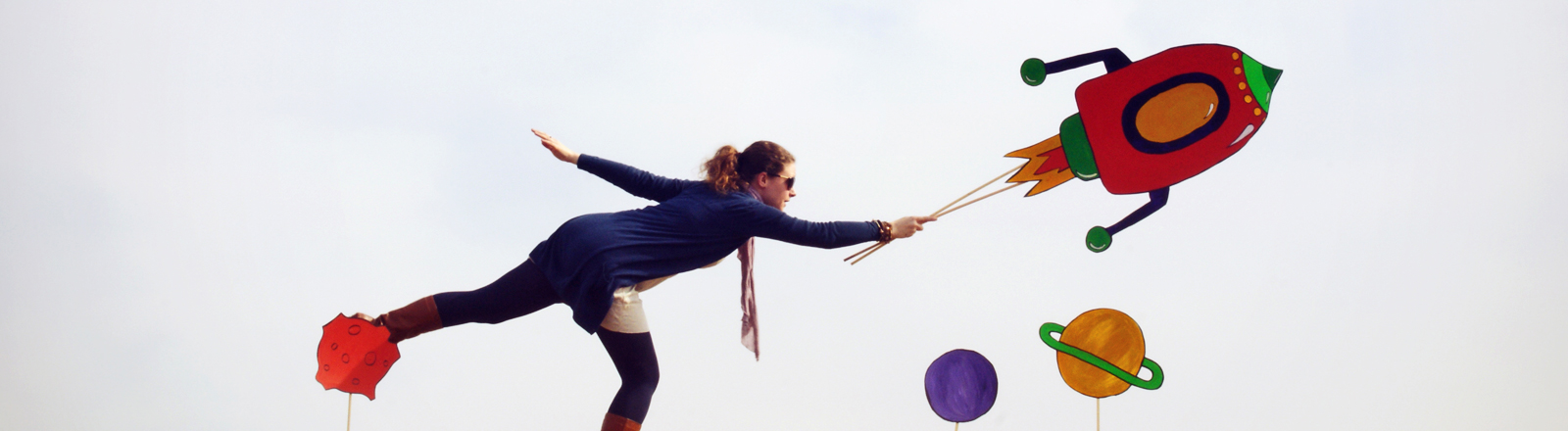 Eine Frau steht auf einem Bein. Sie hält mit der rechten Hand eine gebastelte Rakete.