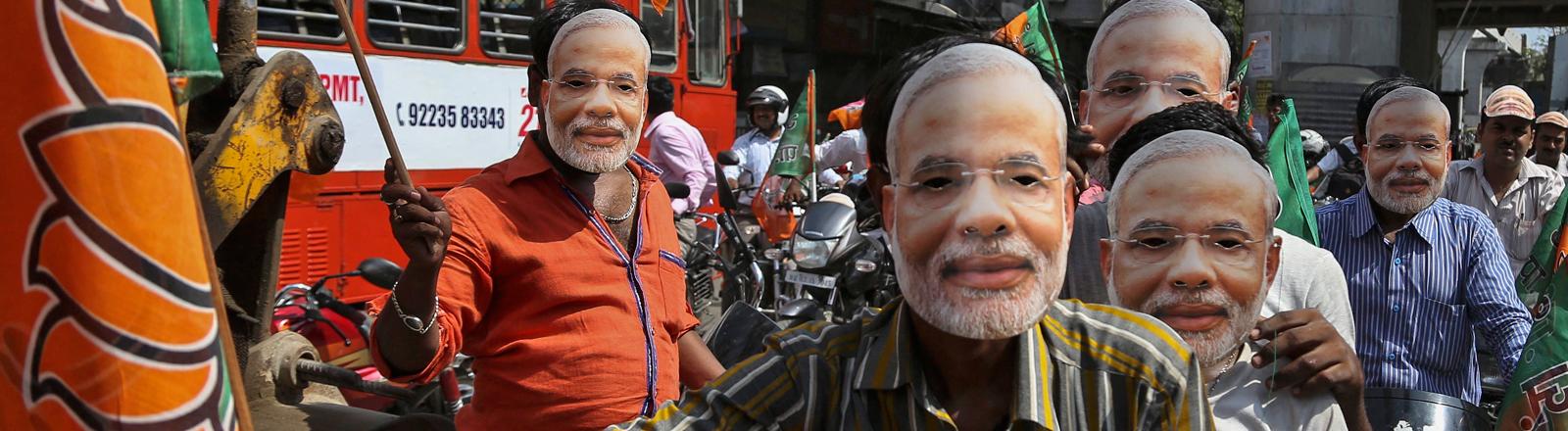 Männer haben sich Pappmasken aufgesetzt, die das Konterfei von Indiens neuem Premier Narendra Modi zeigen; Bild: dpa