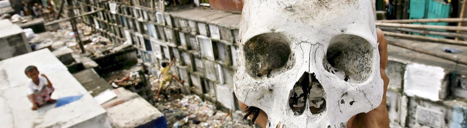 Im Hintergrund sind Gruften zu sehen, im Vordergrund halten zwei Hände einen menschlichen Schädel in die Kamera; Bild: dpa