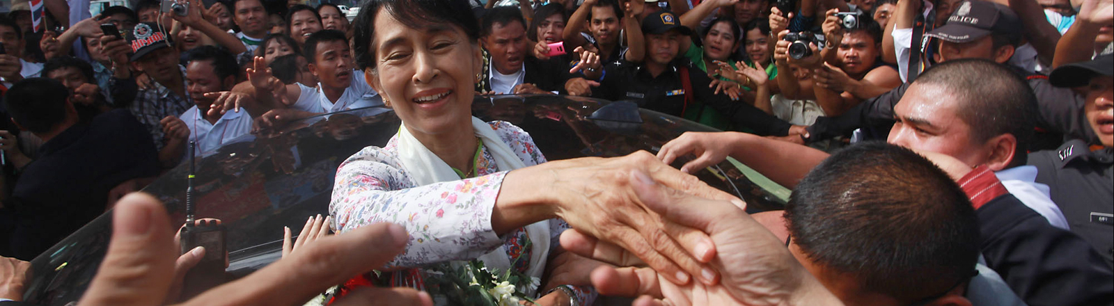 Aung San Suu Kyi lehtn aus dem Fenster eines Autos und schüttelt die Hände von Menschen, die das Auto umstellen. Thailand im März 2012 ;Bild: dpa
