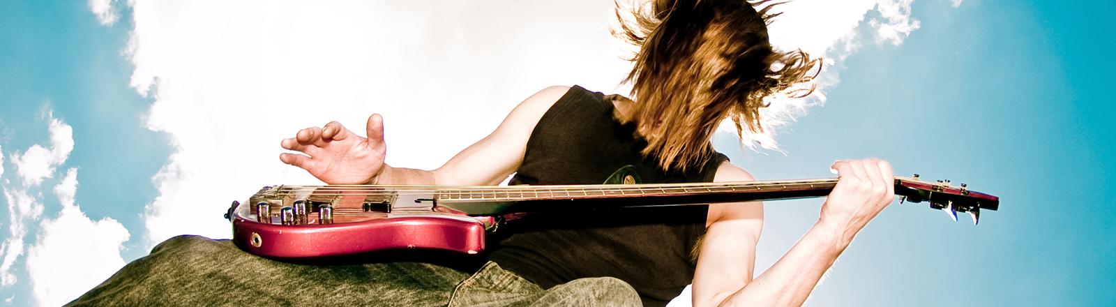 Ein Mann spielt auf einer roten Gitarre. Seine halblangen Haare verdecken sein Gesicht.